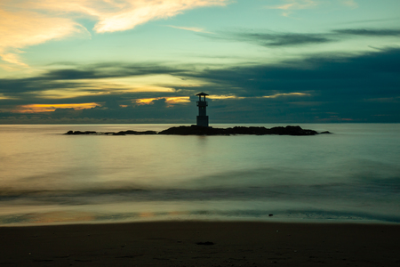 Long exposure image of a small lighthouse against a tropical ocean sunset and smooth water