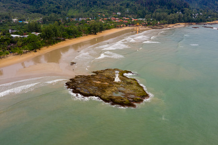 Aerial view of a small lighthouse on a rocky island just off a sandy beach and rough sea