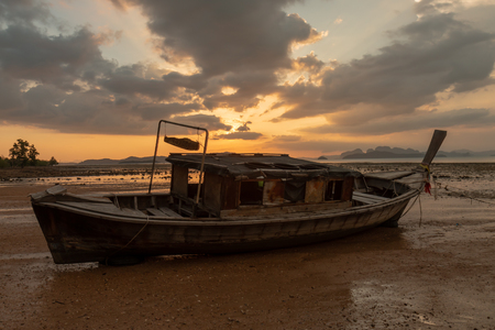 An old wooden boat on a tropical beaching during a beautiful, colorful sunset