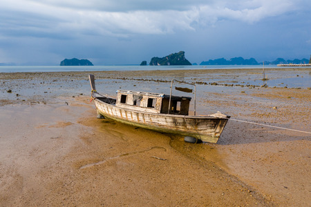 Low aerial view of an old wooden boat stranded at low tide at dusk on a beautiful tropical island