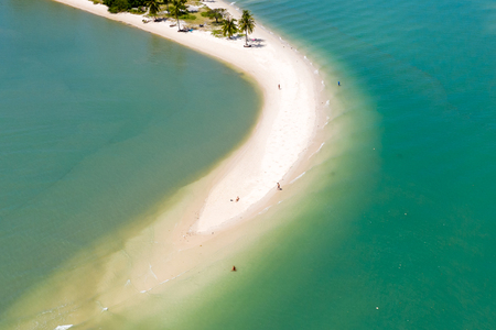 Aerial view of a sand spit leading into the ocean from a green, tropical island