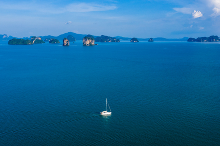 Aerial view of a small sailing boat on a beautiful, flat calm tropical ocean Standard-Bild