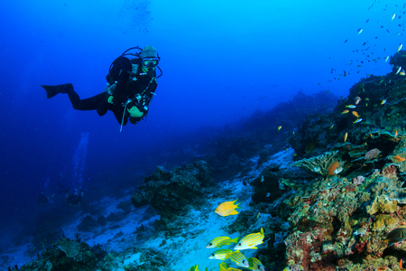 Female SCUBA diver swimming on a tropical coral reef