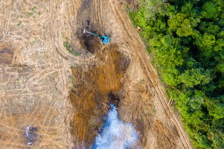 Vogelperspektive der Abholzung des tropischen Regenwaldes. Ein Bagger entfernt Bäume, die dann verbrannt werden