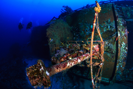 SCUBA divers exploring a deep, underwater shipwreck in a clear, tropical ocean
