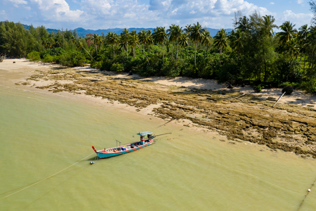 Aerial view of a colorful traditional Thai Longtail boat moored off a small sandy beach in Khao Lak 写真素材