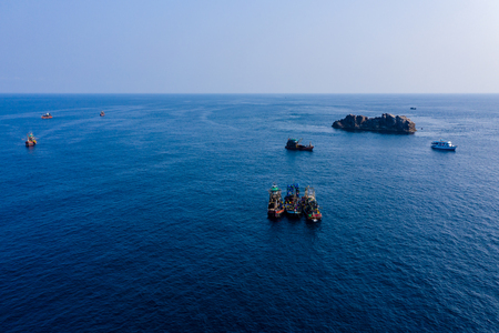Aerial drone view of a fleet of large fishing trawlers surrounding a single SCUBA diving boat at the Black Rock dive site in the Mergui Archipelago, Myanmar