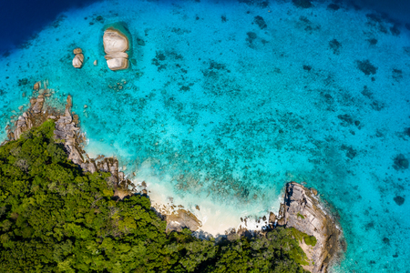 Aerial drone view of a lush tropical island with crystal clear water surrounded by coral reef Imagens