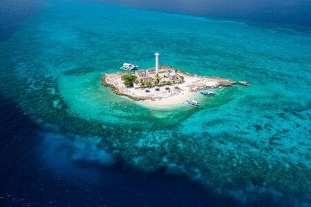 Aerial drone view of a lighthouse on a tiny tropical island surrounded by coral reef and deep water (Capitancillo Island, Cebu, Philippines) Stock Photo