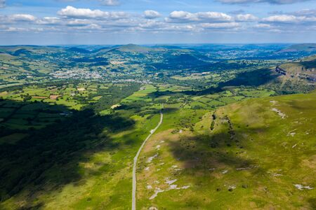 Aerial drone view of a rural road running through green farmland and rolling hills (Llangynidr, South Wales) Banco de Imagens
