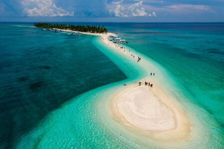 Aerial drone view of people and bangka boats on a tiny, tropical sandspit and coral reef
