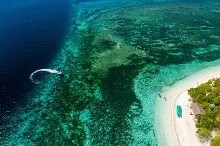 Aerial drone view of a beautiful tropical island surrounded by coral reef and deep ocean (Mantigue Island)