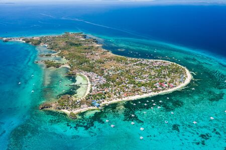 Aerial drone view of a small tropical island and surrounding coral reef (Malapascua)