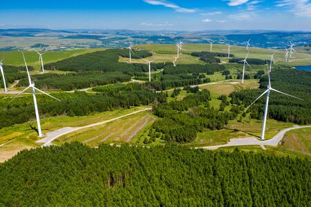 Aerial drone view of a large onshore windfarm on a green hillside