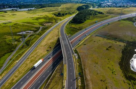 Aerial drone view of a large, new dual carriageway road with motion blurred vehicles (A465, Wales, UK)