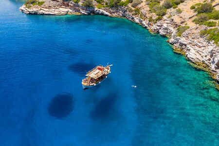 Aerial drone view of a traditional wooden boat on a crystal clear blue ocean (Crete, Greece)