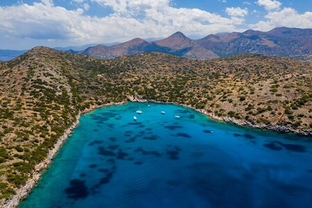 Aerial drone view of a warm, blue, clear ocean with dry coastline and boats (Kolokitha Island, Elounda, Crete)