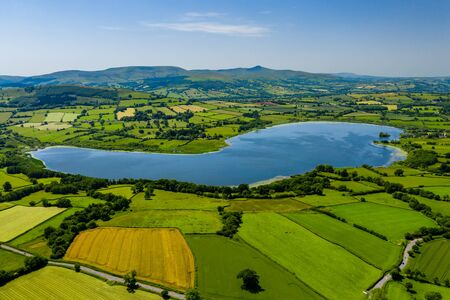 Aerial view of a lake surrounded by green, rolling farmland (Llangorse Lake, Wales)