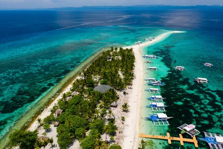 Aerial view of traditional boats moored off a tiny tropical island in the Philippines (Kalanggaman)