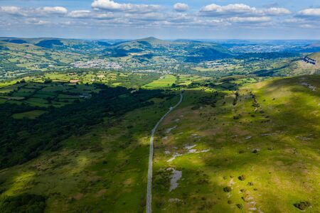 Aerial view of a road running through a rural, hilly landscape in Wales (Llangynidr)