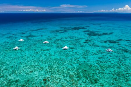 Aerial view of traditional Bangka boats moored above a large tropical coral reef in a calm ocean (Malapascua, Philippines)