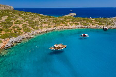 Aerial drone view of traditional Greek wooden boats floating on the crystal clear waters of the Aegean Sea (Crete)
