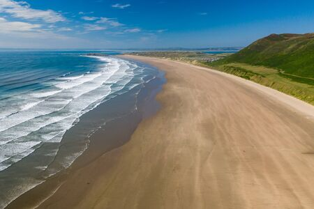Aerial drone view of the beautiful, huge sandy beach at Rhossili on the Gower Peninsula in Wales