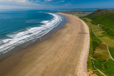 Aerial view of the huge sandy beach and green hills in Rhossili, Swansea