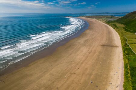 Aerial view of a huge, golden sandy beach and ocean surf