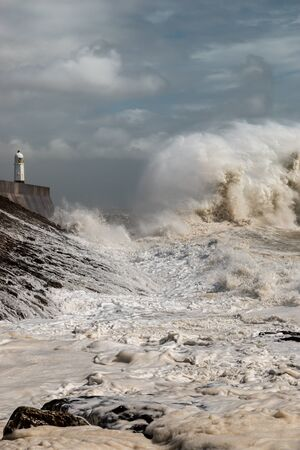 Huge breaking waves next to a lighthouse on a stormy day (Porthcawl, Wales, UK) Stockfoto