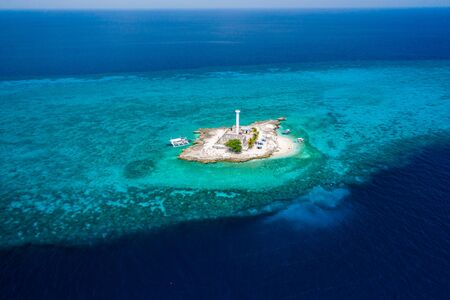 Aerial drone view of tropical Capitancillo Island in the Philippines showing its lighthouse and coral reef