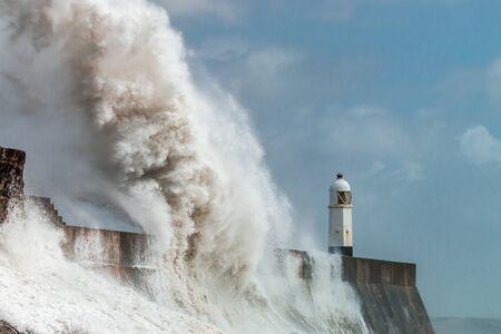 Riesige Meereswellen, die in einen Deich und einen Leuchtturm krachen (Porthcawl, South Wales, UK) Standard-Bild