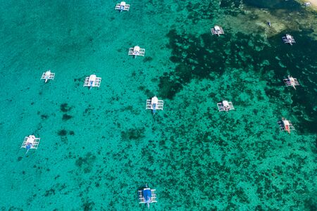 Aerial drone view of traditional wooden boats moored above a shallow water coral reef