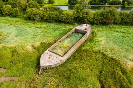Aerial drone view of silt filled hulks of abandoned boats used to reduce erosion on the banks of the River Severn in England (Purton Hulks) Stock Photo