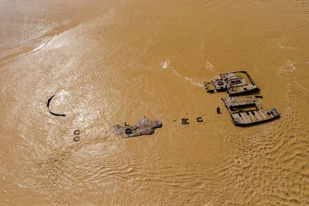 Aerial drone view of rusting hulls of abandoned ships in a brown, muddy river (River Severn)