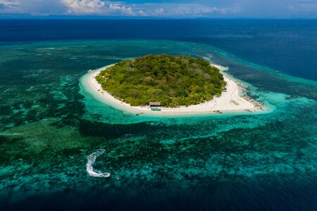 Aerial drone view of a beautiful tropical island and surrounding coral reef