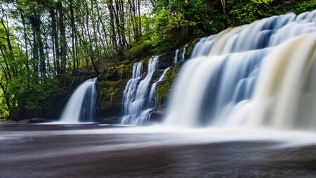 A scenic waterfall surrounded by forest in South Wales (Sgwd y Pannwr, Waterfall country, Wales)
