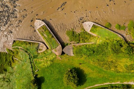 Aerial drone view of silt filled hulks of abandoned boats used to reduce erosion on the banks of the River Severn in England (Purton Hulks) 免版税图像