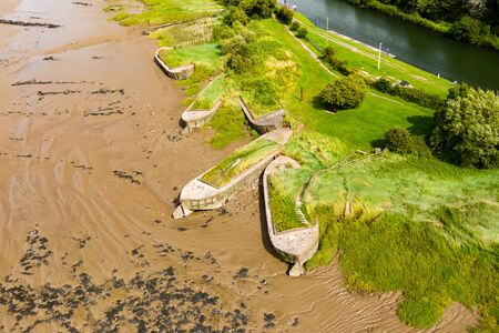 Aerial drone view of silt filled abandoned ships on the banks on a muddy river