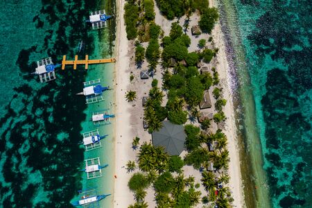 Aerial drone view of traditional Banca boats moored next to a tiny, tropical island surrounded by coral reef (Kalanggaman Island)