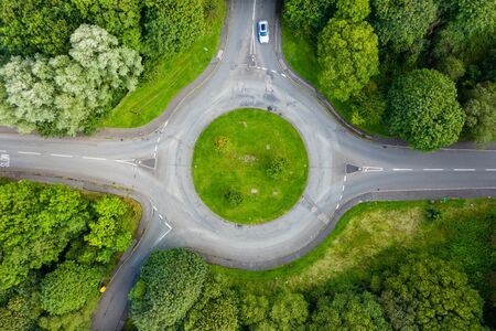 Top down aerial drone view of a small traffic roundabout on a quiet road Stock Photo - 129514241