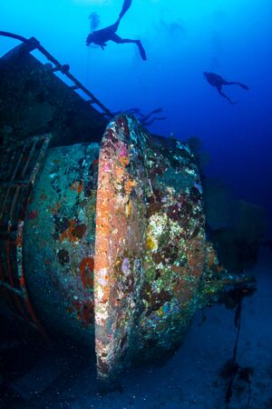 SCUBA divers exploring a large underwater shipwreck in Thailand Stock Photo
