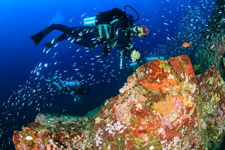 SCUBA Divers on a colorful tropical coral reef in Thailands Similan Islands