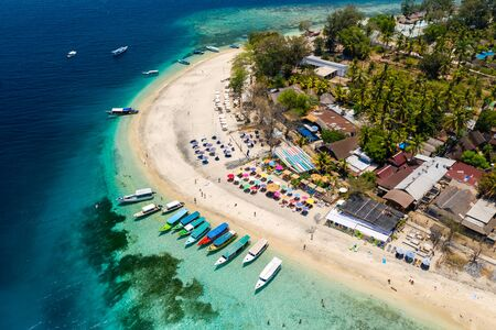 Top down aerial view of colorful boats and sunshades on a tropical beach on a small island fringed by a coral reef Stock Photo