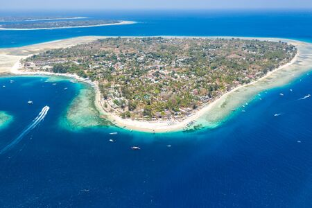 Aerial view of a beautiful tropical island surrounded by fringing coral reef and a deep,blue ocean