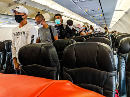 BANGKOK, THAILAND - JUNE 05 2020: Passengers wearing masks queue to disembark a domestic Air Asia flight to Bangkok. Thailand has resumed domestic flights following the Coronavirus pandemic with airlines introducing mandatory mask rules,lower capacity and