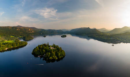 Aerial panorama of sunset next to a beautiful, flat calm lake surrounded by hills (Derwent Water, Keswick, England)