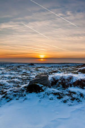 Sunset over a cold, frozen winter landscape on high moorland