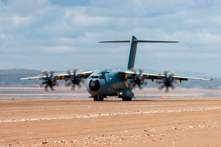 CEFN SIDAN, WALES - MARCH 25 2021: A Royal Air Force Airbus A400M 'Atlas' military transport aircraft practicing tactical landings on the beach at Cefn Sidan Sands in Wales, UK