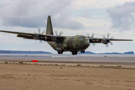 PEMBREY, WALES - APRIL 13 2021: A Royal Air Force Lockheed C-130J 'Super Hercules' performing tactical landings and takeoffs from the public beach at Cefn Sidan Sands in West Wales.